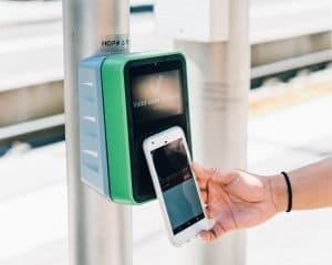 Mobile phone making a payment to a payment reader. ACH could soon become a preferred method of contactless payments.