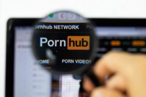 Pornhub logo as seen through a magnifying glass. They were kicked off PayPal recently.