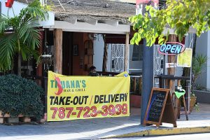 A restaurant banner offering takeout and delivery, one more sign of the pandemic.