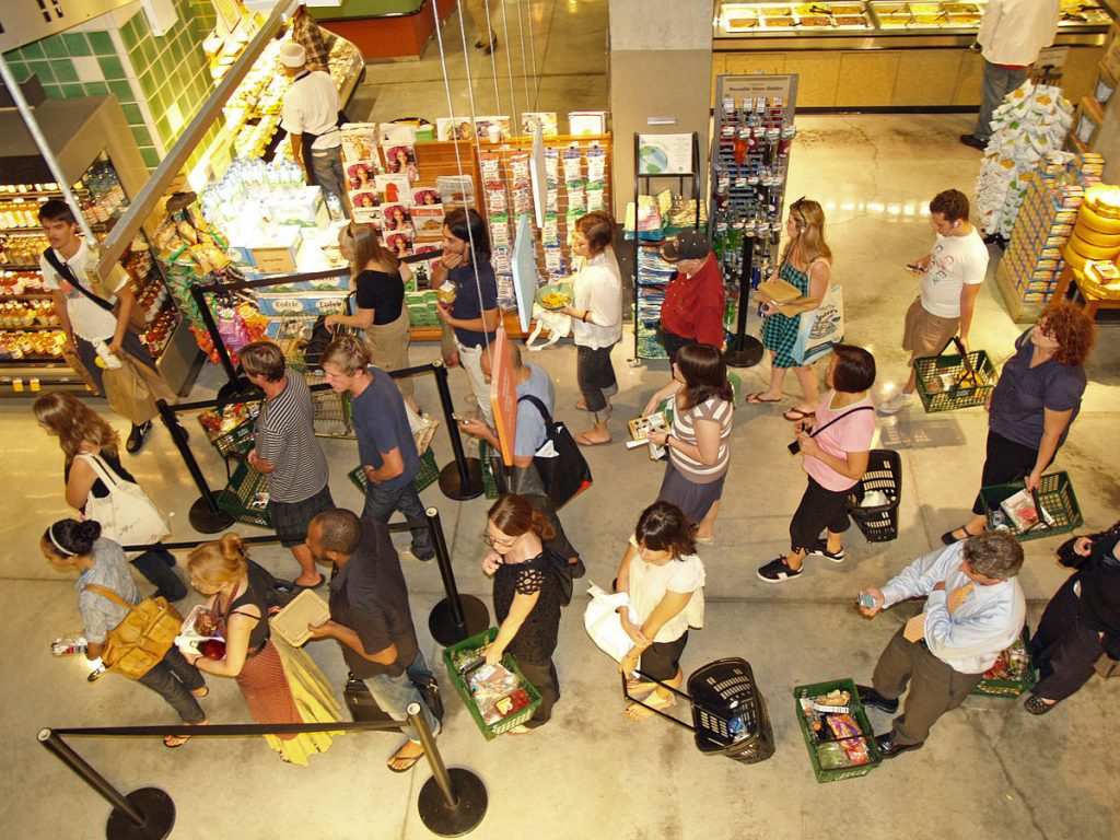 Long line of shoppers at a food store. Returns season will be very busy, so be aware of return fraud.