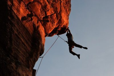 A rock climber suspended over a sheer drop. It looks rather frightening and is a great metaphor for a high-risk merchant.