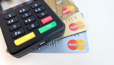 Some Mastercard credit cards and a credit card reader. Mastercard and Visa are postponing their merchant fee increase until 2022.